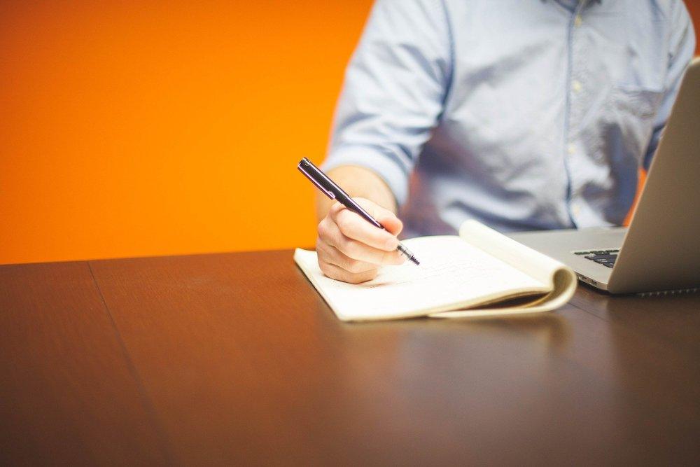 書類を片手にパソコンをする男性